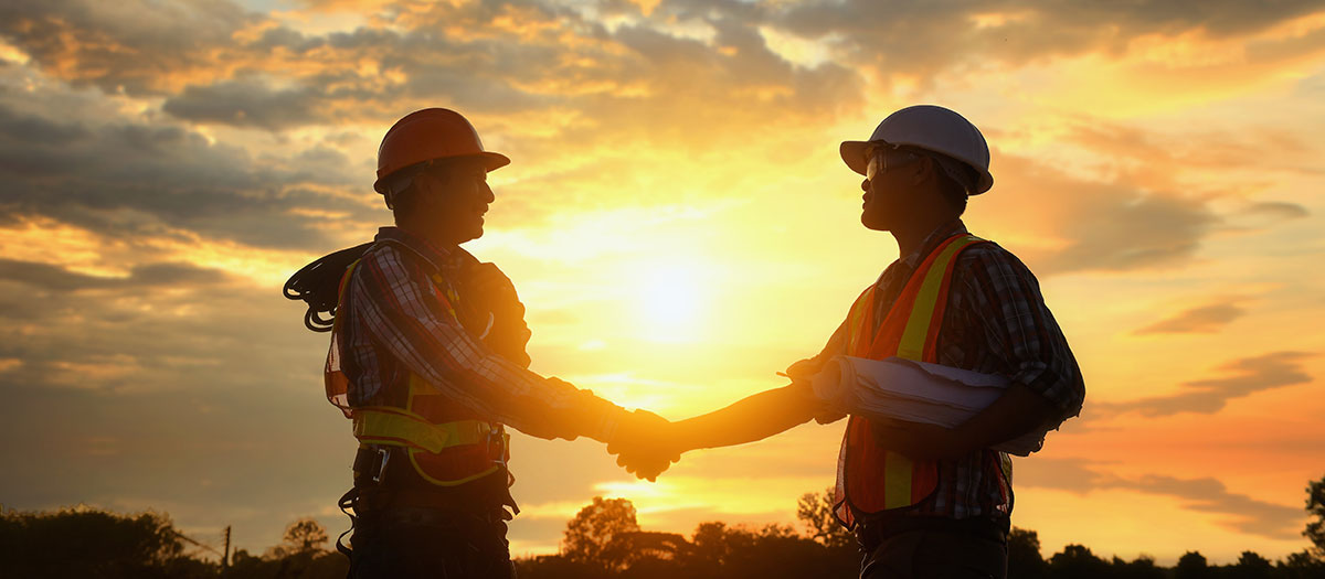 Men shaking hands with sunset behind them